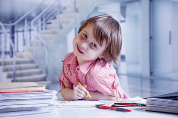 Humorous portrait of child girl designer drawing a pencil sketch (creativity, art, training concept)