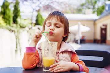 Little cute girl drinking tasty natural smoothie juice outdoors.