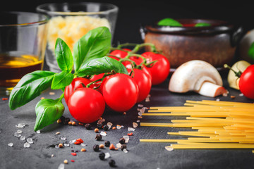Italian pasta ingredients. Cherry-tomatoes, spaghetti pasta, garlic, mushroom, basil, olive oil, mozzarella and spices on dark grunge backdrop