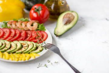Avocado salad on a white background. Avocado, tomato, pepper and shrimps on a plate lined with rows