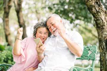 Happy senior Asian couple using smartphone