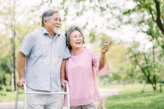 Happy senior couple talking a walk with walker