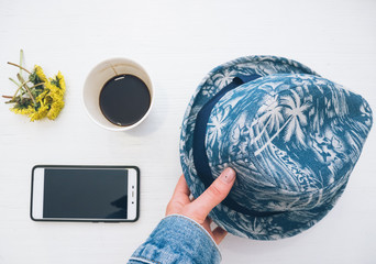 flatlay of phone coffee sandwich flower hat