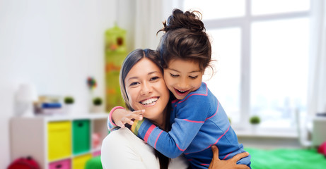 family, motherhood and people concept - happy mother and daughter hugging over over kids room at home background