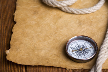 antique compass and rope on vintage paper background