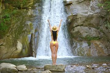 Beautiful woman relaxing near waterfall