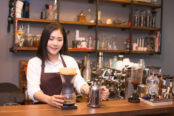 Asian women Barista smiling and looking to camera in coffee shop counter.  Barista female working at cafe. Working woman small business owner or sme concept.