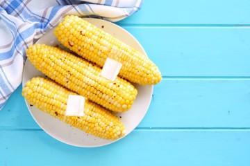 Summer corn on the cob. Top view on blue wood background.