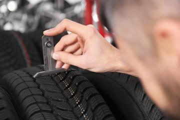 Mechanic measuring tire tread depth in automobile service centre