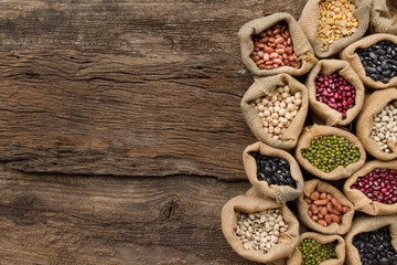 Legumes seed in sack on wooden background, top view. Protein from bean is best nutrition for vegan food
