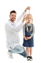 Doctor measuring little girl's height on white background
