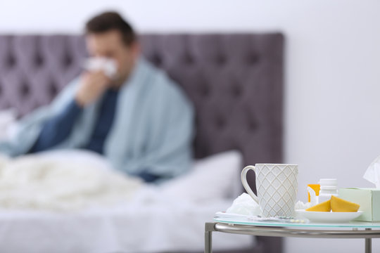 Table with cold remedies and blurred sick man on background
