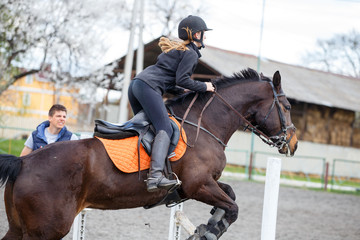 Young girl on bay horse jumping over hurdle in show jumping training