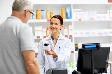 medicine, pharmaceutics, healthcare and people concept - apothecary and senior male customer buying drug at drugstore