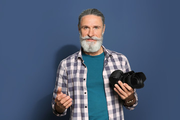 Male photographer with professional camera on color background