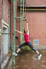 Sportliche Frau trainiert Fitness an Hauswand
