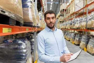 logistic business, shipment and people concept - businessman with clipboard at warehouse