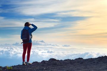 Tourist admiring breathtaking sunset views from the Mauna Kea, a dormant volcano on the island of Hawaii.