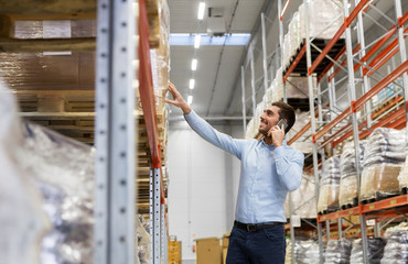 wholesale, logistic business and people concept - smiling businessman calling on smartphone at warehouse