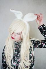 Mujer joven y rubia que lleva puestas unas orejas de conejo