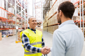 logistic business and cooperation concept - manual worker and businessman with clipboard shaking hands and making deal at warehouse