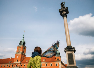 Girl with flying scarf against Royal Palace and Sigismund's Column III Waza monument in Historic...