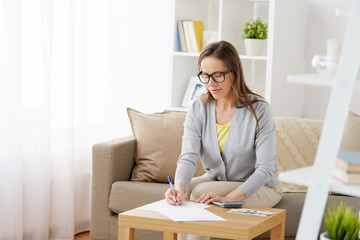 business, savings, finances and people concept - middle-aged woman with papers, money and calculator at home