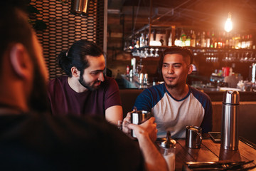Group of mixed race young men drinking tea in lounge bar. Middle-eastern friends having fun in cafe