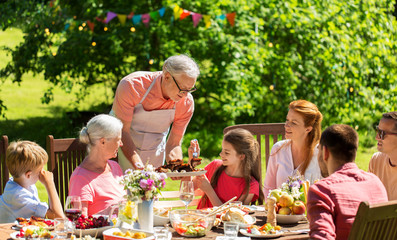 leisure, holidays and people concept - happy family having festive dinner or summer garden party