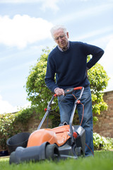 Senior Man Suffering With Backache Whilst Using Electric Lawn Mower To Cut Grass At Home