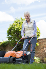 Senior Woman Using Electric Lawn Mower To Cut Grass At Home