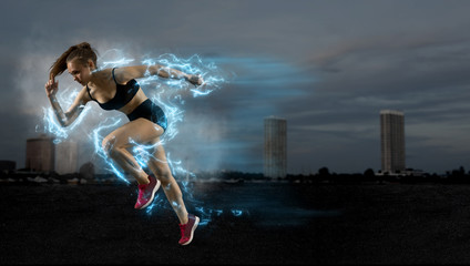 Woman sprinter leaving starting blocks on the athletic track