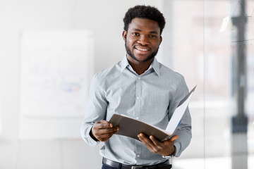 Fototapeta business, people and corporate concept - smiling african american businessman with folder at office obraz