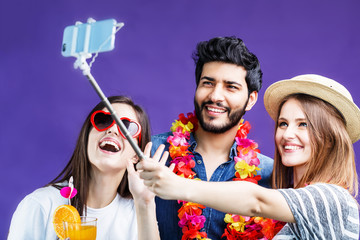 Happy smiling friends, two girls and bearded man, make selfie photo via smartphone before purple background