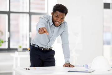 architecture, construction business and people concept - smiling african american architect with blueprint working at office pointing at you