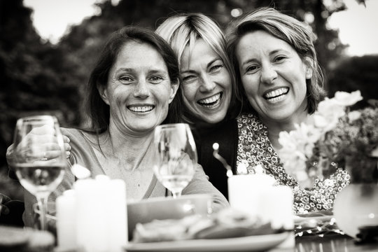 looking at the camera, three female friends in their 40s share a moment of complicity. They gathered around a table in the garden to share a meal with friends.
