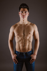Handsome topless man standing in jeans