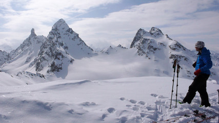 backcountry skier on the summit of a remote alpine peak enjoys the great view of a mountain landscape in front of him