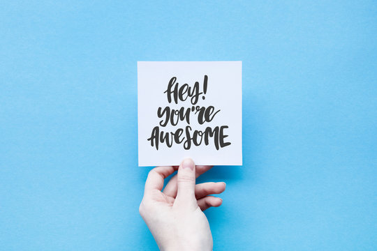 Minimal composition on a blue punchy pastel background with girl's hand hold card with quote - Hey! You're awesome