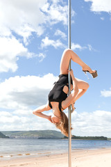 dancer on pole performs acrobatic