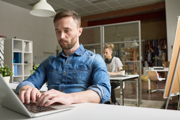 Portrait of handsome bearded businessman wearing casual clothes  using laptop sitting at desk in modern open space office, young colleague behind him, copy space