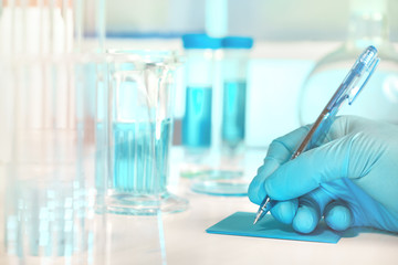 Biological or biochemical lab out of focus, closeup on gloved hand writing a note