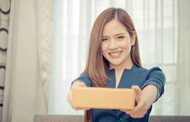Woman is handing package box from online shopping