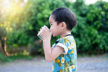 Asian Cute Boy drinking water for Healthy and Refreshing with green tree background.