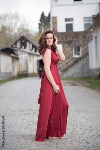 d399c5a6deb61 erotische junge Frau in langen roten Kleid auf altem Fabrikgelände ...