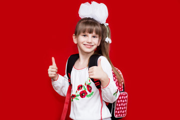 Cute smiling little girl in school uniform and white bows with backpack on red background. Back to school. Education and school concept