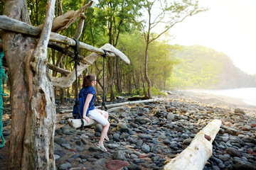 Young female tourist relaxing on a handmade swing on rocky beach of Pololu Valley on Big Island of Hawaii