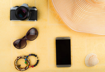 Women's accessories for a beach holiday. A smartphone with a blank screen, a striped hat, jewelry, sun glasses, film camera and a shell in the background of a yellow terry towel.