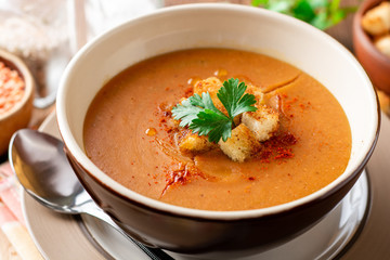 Red lentil cream soup with croutons in bowl on wooden table