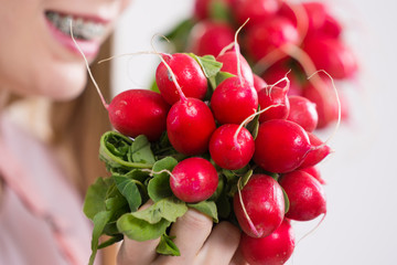 woman holding radish close to face
